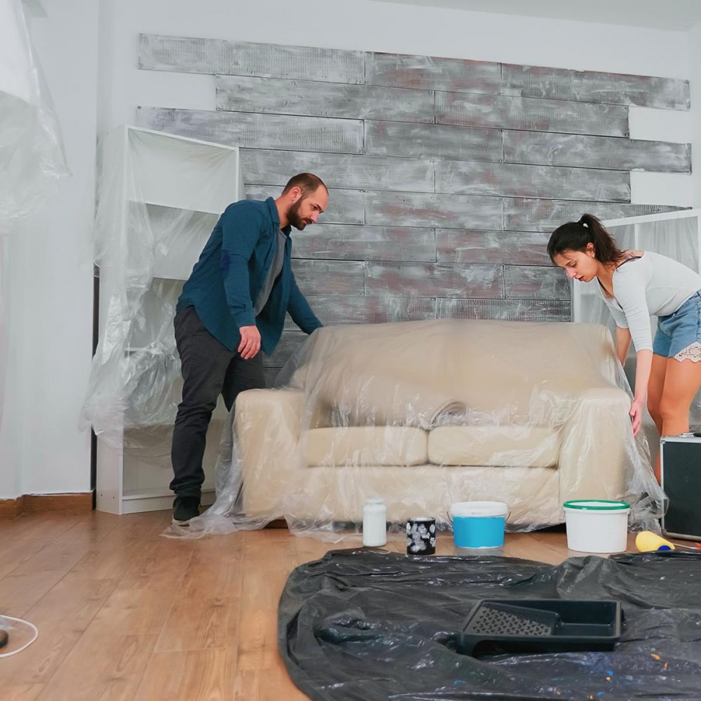 Married couple covering sofa with plastic sheet for home decorating. Apartment redecoration and home construction while renovating and improving. Repair and decorating.